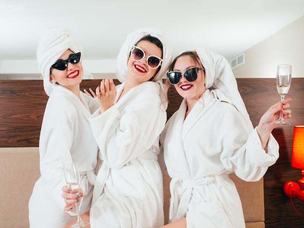 Meninas alegres em roupões de banho e turbantes de toalha. champanhe e óculos de sol. tempo de lazer do ponto de encontro das mulheres.