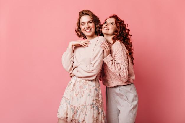 Meninas alegres, expressando felicidade em fundo rosa. vista frontal de duas senhoras bem vestidas, sorrindo para a câmera.