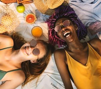 Meninas alegres no banho de sol sol bronzeamento juntos
