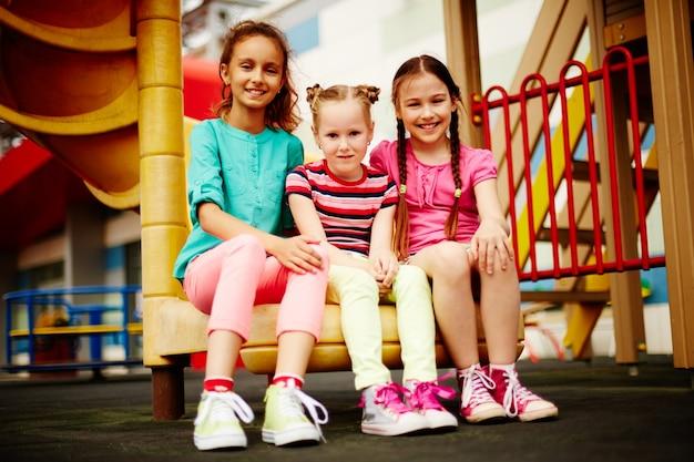 Meninas alegres sentam ao ar livre