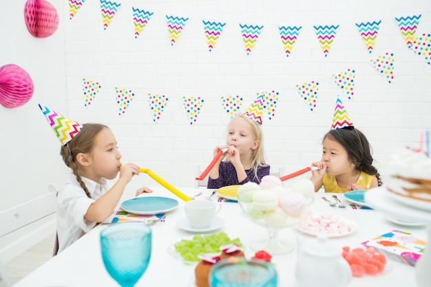 Meninas alegres soprando cornetas de festa