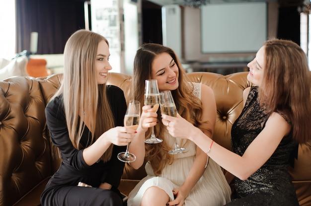 Meninas alegres tilintar de copos de champanhe na festa