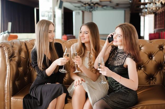 Meninas alegres tinindo copos de champanhe na festa