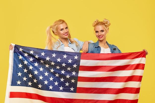 Meninas americanas. felizes mulheres jovens em roupas jeans, segurando a bandeira dos eua isolada em fundo amarelo