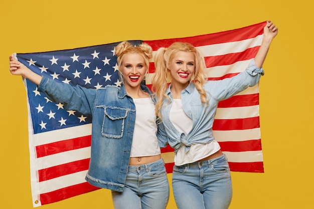 Meninas americanas. jovens mulheres felizes na roupa da sarja de nimes que mantêm a bandeira dos eua isolada no fundo amarelo. fã de futebol