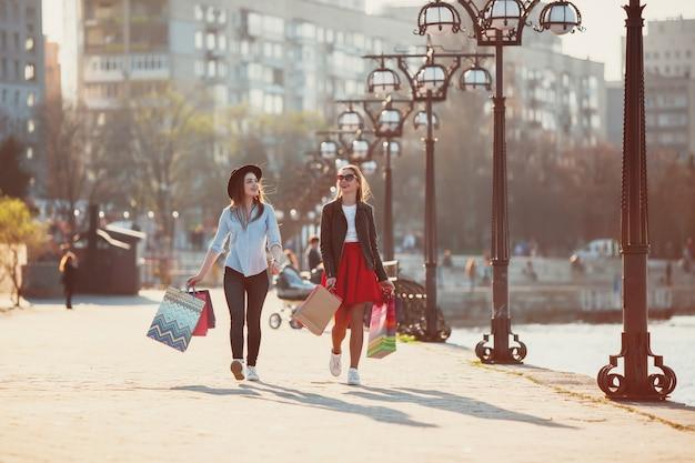Meninas andando com as compras nas ruas da cidade