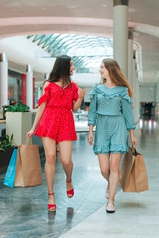 Meninas andando com suas malas no shopping