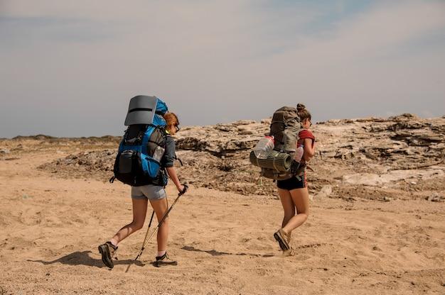 Meninas andando no deserto com mochila para caminhadas