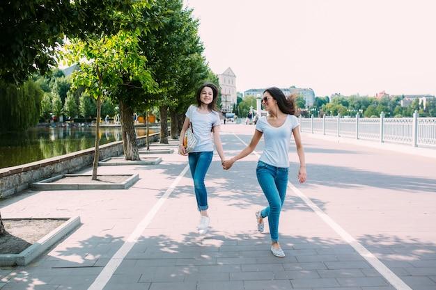 Meninas andando no pavimento de mãos dadas