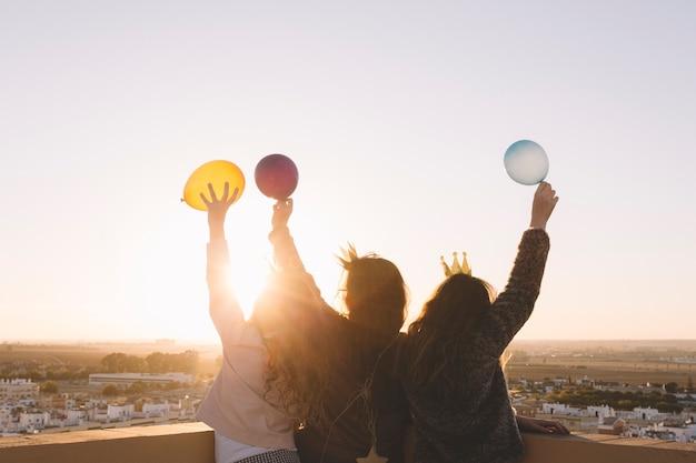 Meninas anônimas com balões no telhado