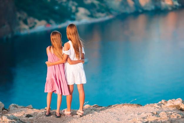 Meninas ao ar livre na beira do penhasco apreciar a vista sobre a rocha no topo da montanha ao pôr do sol