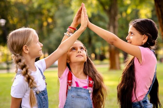 Meninas, apertando as mãos no ar