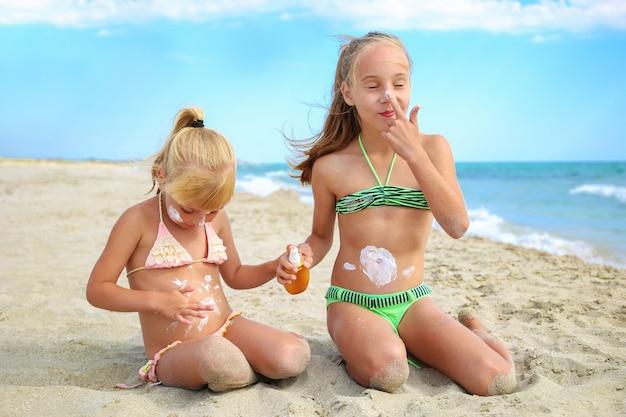 Meninas aplicando suncream na praia