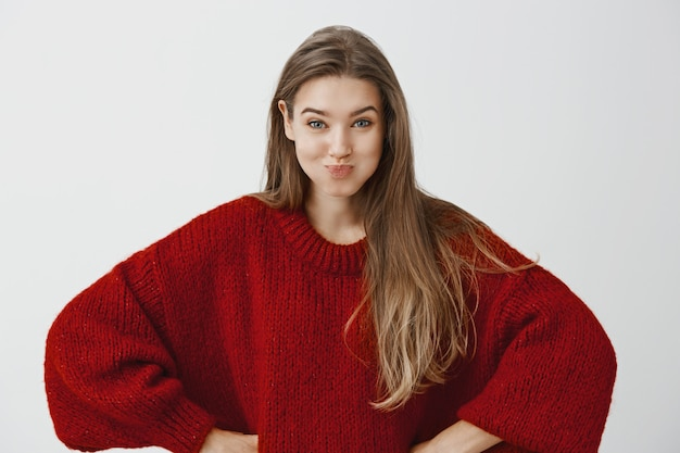 Meninas apostando quanto tempo elas conseguem prender a respiração. foto interior da mulher feminina atraente infantil elegante suéter solto vermelho, de mãos dadas nos quadris e de mau humor divertidamente