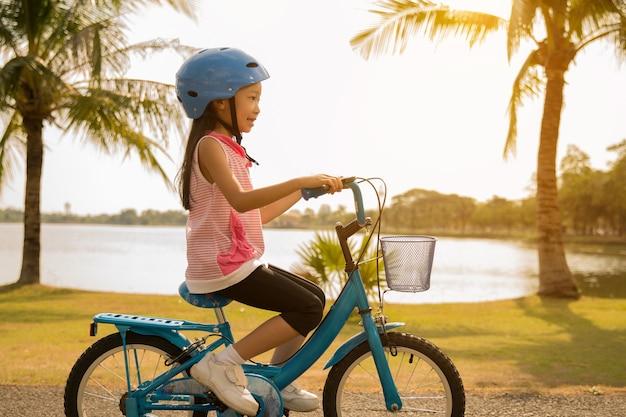 Meninas asiáticas, andar de bicicleta no parque de manhã