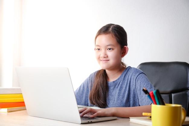 Meninas asiáticas aprendem online em casa por meio de videochamadas usando um laptop para se comunicar com os professores.
