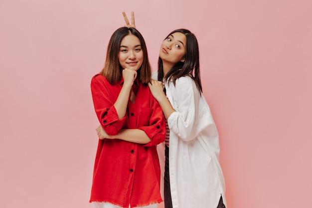 Meninas asiáticas atraentes e charmosas se divertem e fazem caretas engraçadas na parede rosa