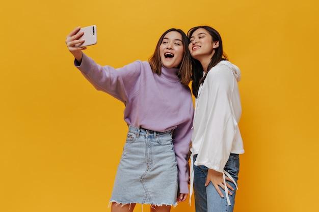 Meninas asiáticas atraentes em trajes de ganga sorrindo e tirando selfie isoladas