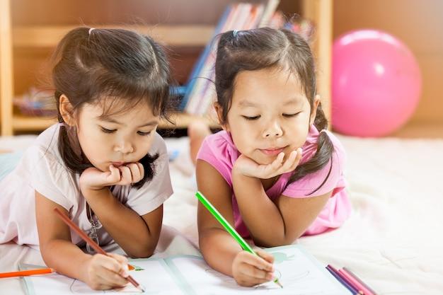 Meninas asiáticas bonitas desenham com seus crayons. tom de cor vintage