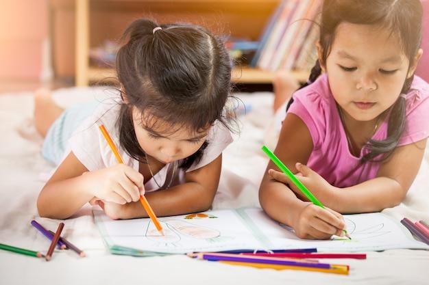 Meninas asiáticas bonitas desenham com seus crayons. tom de cor vintage Foto Premium