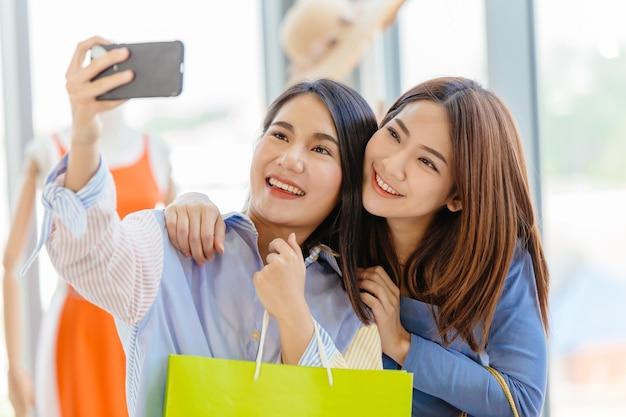 Meninas asiáticas com amigo feliz desfrutar de compras divertidas selfie momento de felicidade na loja juntos.