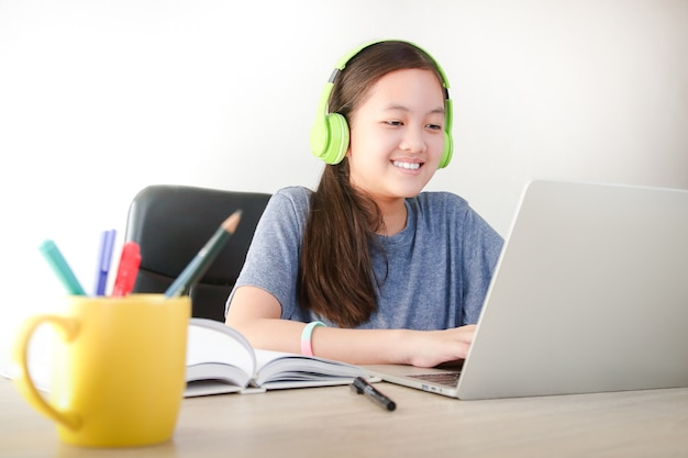Meninas asiáticas estudam online em casa por videochamada, usando um notebook para se comunicar com os professores. conceito educacional, distanciamento social para reduzir a propagação do coronavírus (covid-19)
