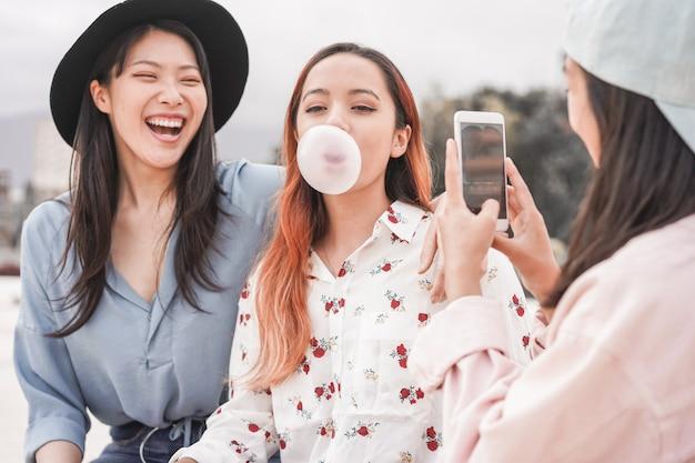 Meninas asiáticas felizes fazendo história em vídeo para o aplicativo de rede social ao ar livre - amigos das jovens mulheres se divertindo fazendo feeds ao vivo - tendências da nova tecnologia e conceito de amizade - foco na pessoa soprando