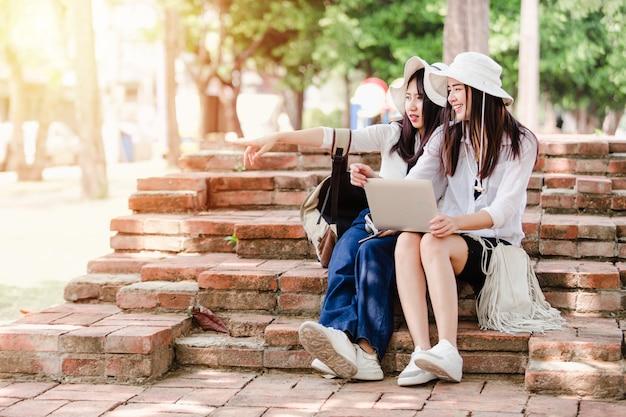 Meninas asiáticas jovens e amigos viajante na cidade, duas mulheres sentadas usam busca laptop para atrações