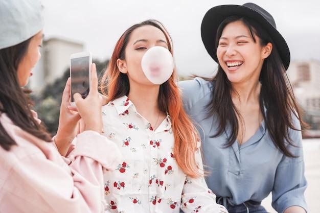 Meninas asiáticas na moda fazendo história em vídeo para aplicativo de rede social ao ar livre