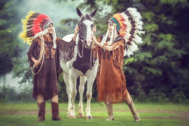 Meninas asiáticas novas da beleza com mulher do nativo americano e passeio com o cavalo americano da pintura em tailândia.