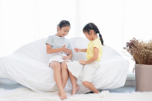 Meninas asiáticas tocando juntos em uma sala branca