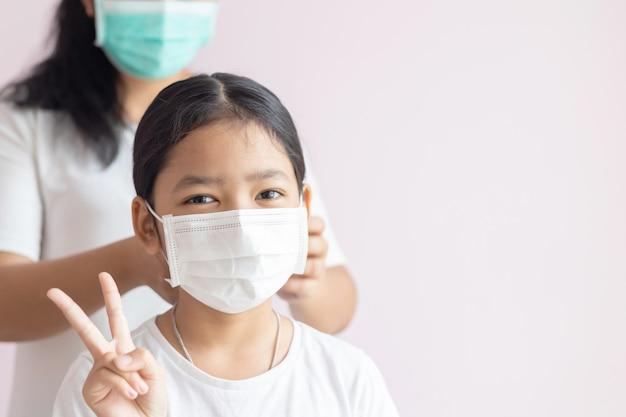 Meninas asiáticas usam máscaras de proteção médicas e levantam 2 dedos