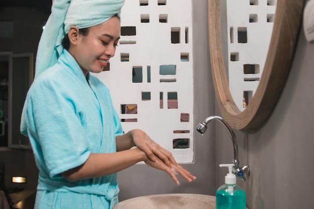 Meninas asiáticas usam toalhas de banho e lavam as mãos com sabonete até formarem espuma na pia