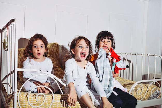 Meninas assustadas em pijamas assistindo tv