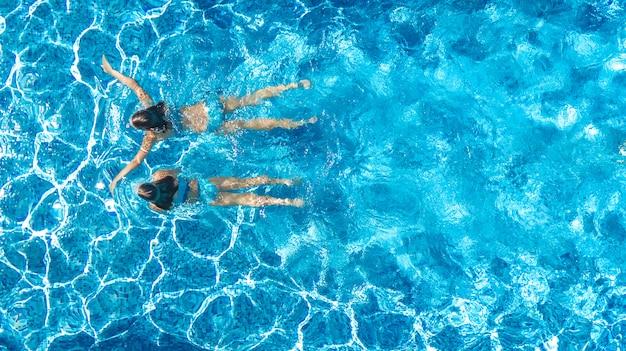 Meninas ativas na piscina água zangão aéreo vista de cima, crianças nadam, crianças se divertem em férias em família tropical, conceito de resort de férias