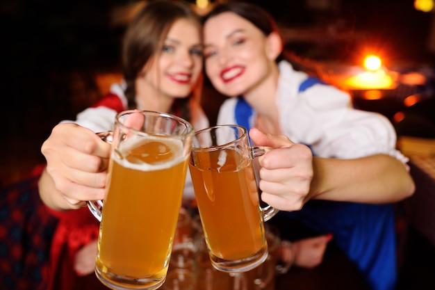 Meninas atrativas em vestidos bávaras sentado em uma mesa em um bar.