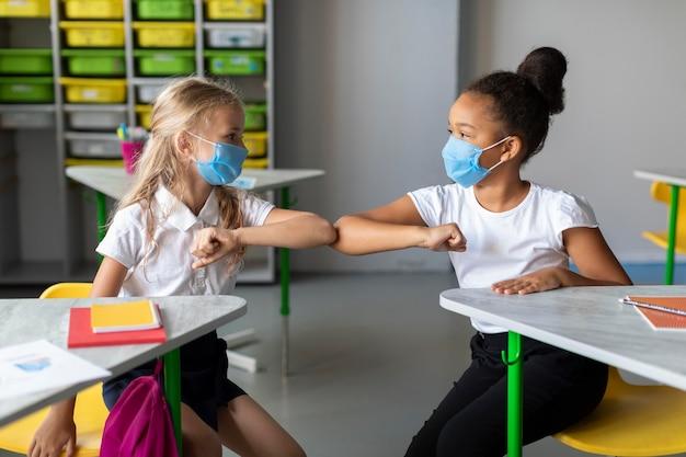 Meninas batendo o cotovelo na sala de aula