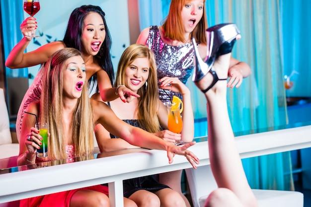 Meninas bêbadas com cocktails extravagantes no clube de strip