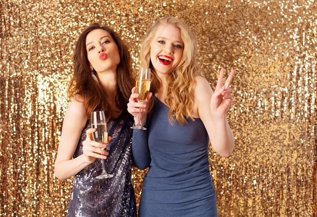 Meninas bebem vinho espumante para comemorar o ano novo