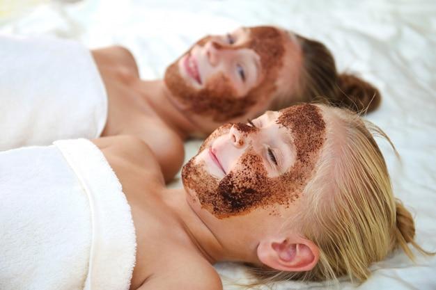Meninas bonitas com esfoliação facial café máscara.