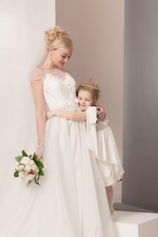 Meninas bonitas com flores vestidas em vestidos de noiva