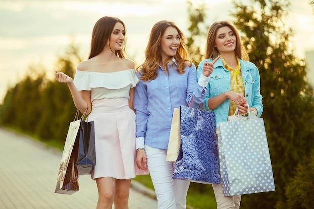 Meninas bonitas com pacotes depois de fazer compras uma foto de um grupo de amigos felizes, fazer compras na cidade. menina andando pela cidade depois das compras. bom humor. luz da noite. conceito de compras