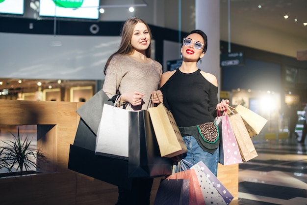 Meninas bonitas com sacolas de compras estão olhando para a câmera e sorrindo enquanto fazia compras no shopping