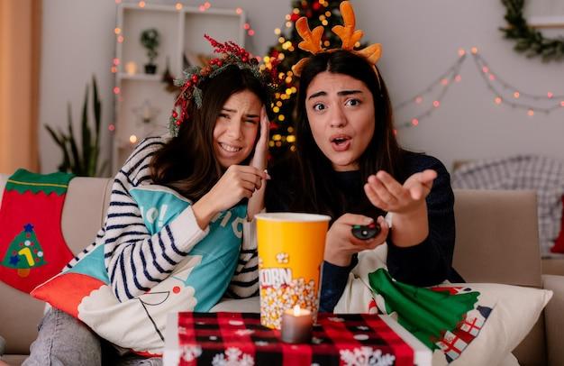 Meninas bonitas descontentes com coroa de azevinho e bandana de rena olham para a câmera sentadas em poltronas na época do natal em casa