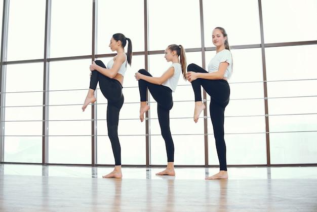 Meninas bonitas e elegantes fazendo yoga