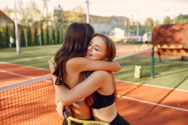 Meninas bonitas e elegantes na quadra de tênis