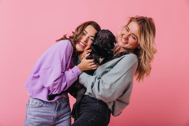 Meninas bonitas em roupa casual, rindo enquanto posava com um lindo cachorrinho preto. foto interna dos melhores amigos segurando bulldog francês.