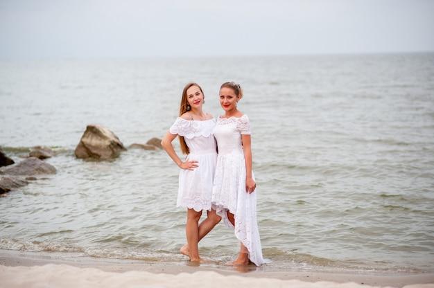 Meninas bonitas em vestidos brancos fotografados no mar