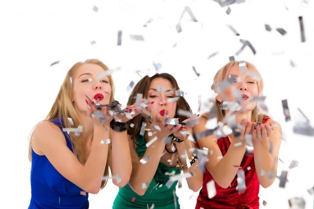 Meninas bonitas em vestidos brilhantes soprando em confete em uma festa em um estúdio em branco