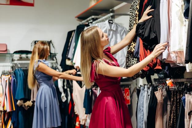 Meninas bonitas escolhem roupas na sala de exposições